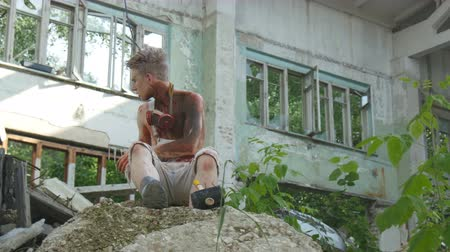 maniac : Maniac sits on a rock in an old building removes a mask and lights a cigarette Stock Footage