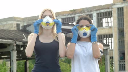 destruir : Two girls put on yellow glasses and lower their hands
