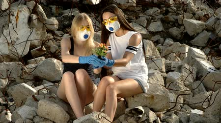 aftermath : Girls sit among the ruins debris and inspect a plant Stock Footage