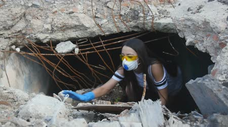 aftermath : Girl in yellow glasses and a respirator gets out from a hole in the ground Stock Footage