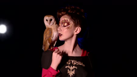 сказка : Fairy girl with an owl on her shoulder in a dark place