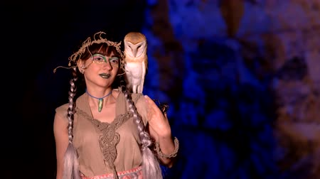 faerie : Fabulous woman with an owl on her shoulder in a dark cave
