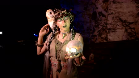 faerie : Woman in medieval clothes with a glowing skull and an owl in a cave Stock Footage