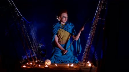 faerie : Fairy tale woman with make up looks at the sword on a wooden suspension bridge Stock Footage