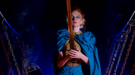 greasepaint : Fairytale woman with make up looks at the sword on a wooden suspension bridge
