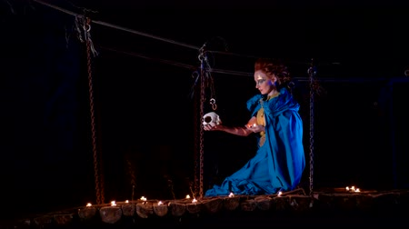 faerie : Fairy girl sits on a suspension bridge and holds a skull and candle in her hands