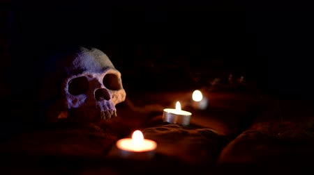 buried : Skull and candles and smoke in the dark