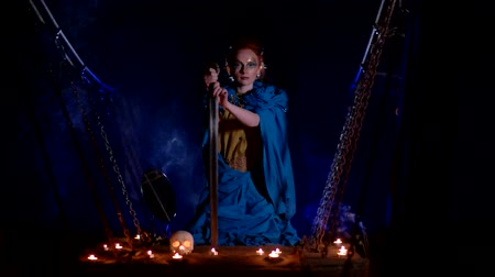 faerie : Fairy girl with a sword in her hand sits on a suspension bridge among candles