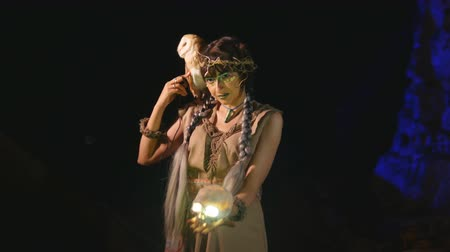 faerie : Fancy woman in medieval clothes with a glowing skull and an owl in a cave Stock Footage