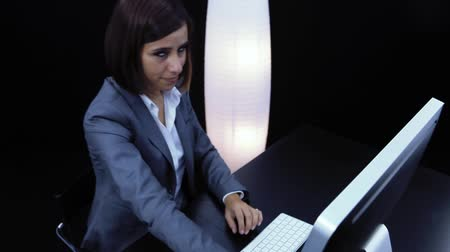 Woman works at the computer and showing a card with text