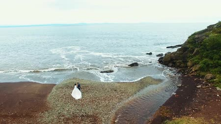 csak : Aerial view of wedding couple standing on a rocky beach