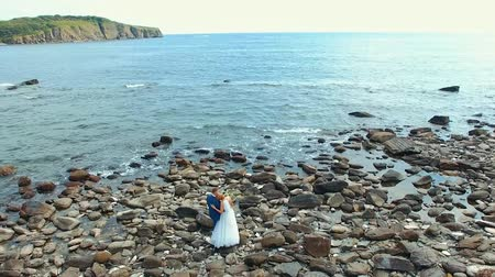 marad : aerial view wedding couple standing on the stones of a rocky beach
