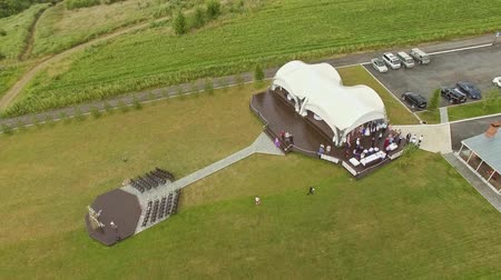 malikâne : aerial orbit wedding ceremony with arch decorated with cloth and flowers outdoor Stok Video
