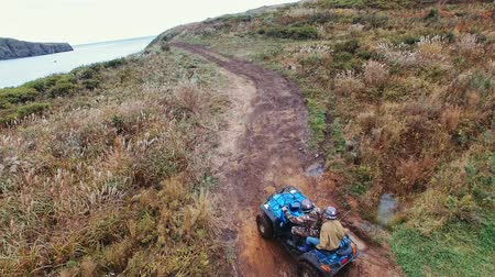 atv : aerial view young couple of tourists is riding on ATV transport on the edge of cliff Couple is riding on a quad bike and enjoy view sea