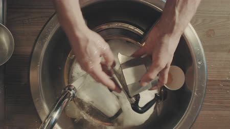 spoons : Mans hands washing dishes in the kitchen after breakfast
