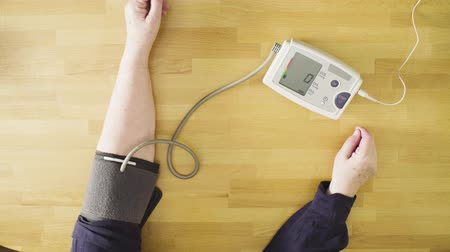 hypertension : Senior woman measuring her own blood pressure Stock Footage