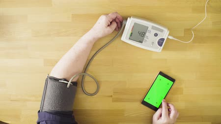physical pressure : Senior woman measuring her own blood pressure Stock Footage
