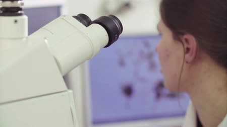 reseach : Young woman scientist near the microscope Stock Footage