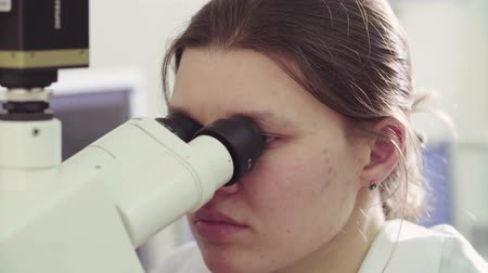 reseach : Scientist looking into eyepieces of a microscope Stock Footage