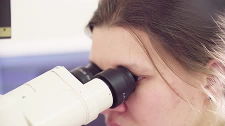 obter : Scientist looking into eyepieces of a microscope Stock Footage