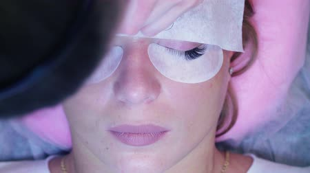 szempillák : Woman face. Eyelash extension procedure in salon