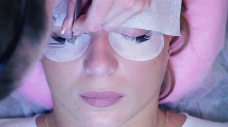 extremely : Woman face. Eyelash extension procedure in salon