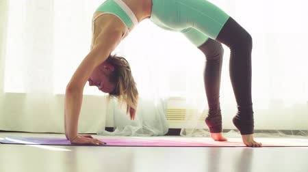 gymnastics : Young woman doing yoga asanas in studio. Stock Footage