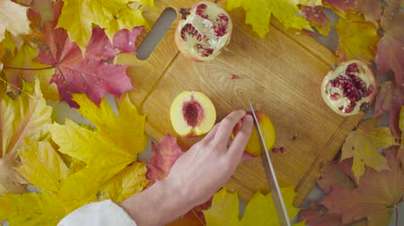 granate : Naturemorte de otoño. Chef cortando un durazno