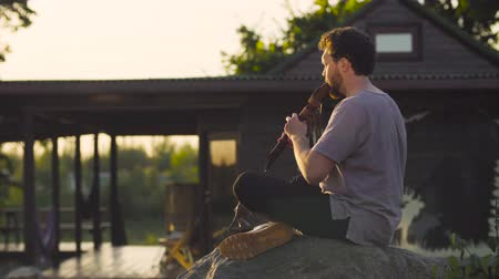 fuvolák : A man sitting on a rock and playing ethnic flute