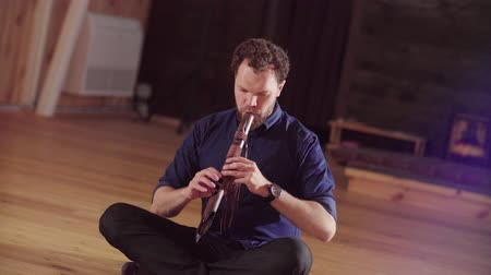 flutist : A man sitting on the floor and playing flute