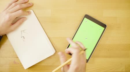marker : Green screen. Male hands scrolling a tablet
