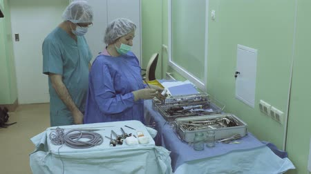 működés : Surgical nurse preparing instrument for operation