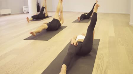 reclináveis : Yoga class. Reclining hand-to-big-toe pose