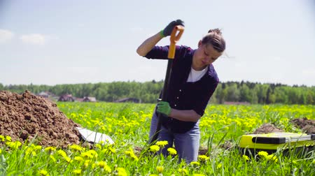 naturalist : Woman ecologist on the meadow digging a soil slit Stock Footage