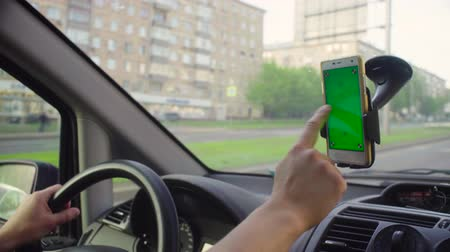 дисплей : Someone driving a car and scrolling smart phone
