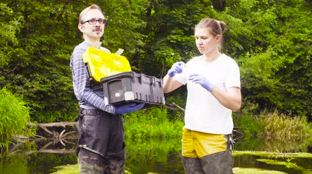 waders : Woman ecologist taking samples of water