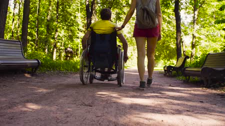 rokkant : Young disable man with his wife on a walk in the park