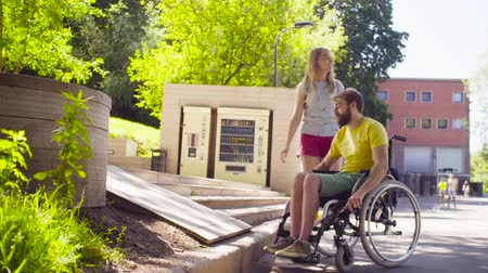invalidní vozík : Young disable man on a walk in the park with his wife