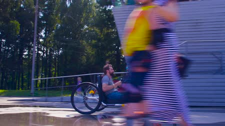 inwalida : Happy young disable man is riding hand bike