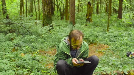 conservationist : The ecologist in a forest with smart phone