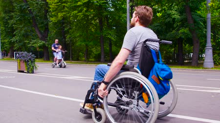handikap : Young disable man walking in the park in wheelchair
