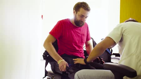 inwalida : Doctor putting the robotic exoskeleton for disabled man