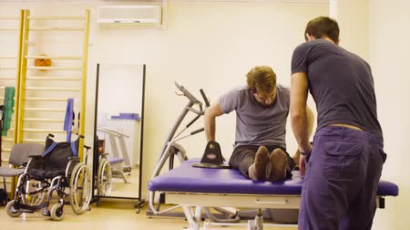 inwalida : Doctor physiotherapist explains to the patient how to do the exercise