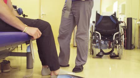 handikap : Doctor physiotherapist putting the orthosis for disabled man Stok Video