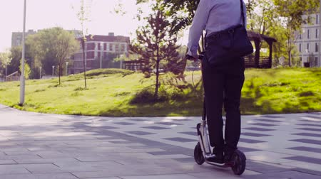 mobilet : A man in a business suit riding a kick scooter Stok Video