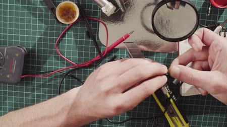 tester : Male hands repairing wire for electronic devices.