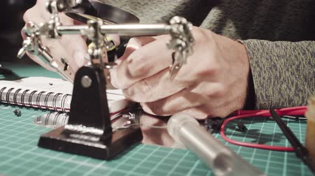 magnifier : Male hands repairing wire for electronic devices.