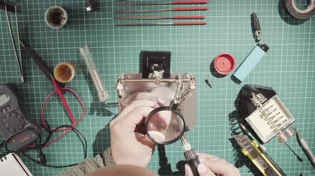 magnifier : Male hands soldering wire Stock Footage