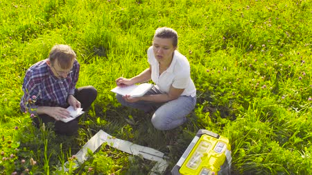 environmentalist : Two ecologist examining plants on the meadow Stock Footage