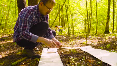 on site research : The man ecologist describes the plants inside the square marking site. Stock Footage